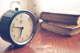 stock photo of analog clock  - analog retro alarm clock on wooden table - JPG