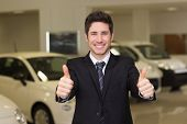 Smiling businessman giving thumbs up at new car showroom