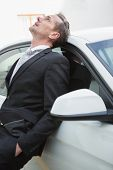 Upset businessman leaning on his car in a car park