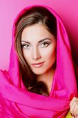 Beauty portrait of a positive young woman in bright crimson headscarf over pink background. Beauty, fashion. Cosmetics.