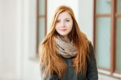 picture of redheaded  - Portrait of young beautiful redhead woman wearing coat and scarf posing outdoors with architectural background - JPG