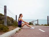 Sporty young woman sitting on the path