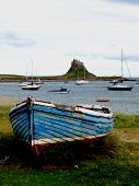 stock photo of boat  - Lindisfarne Castle in the distance over looked from the harbour - JPG