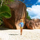 Woman at beautiful beach wearing rash guard. Seychelles, Praslin, Anse Lazio