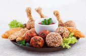 Various fried chicken appetizers with tomato dip
