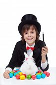 Young magician boy preparing for easter - conjuring a white rabbit and colorful eggs