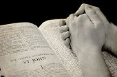 foto of prayer  - Hands of a person raised together in prayer with bible - JPG