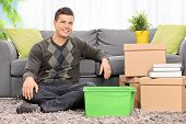 Man seated on the floor by a bunch of boxes at home