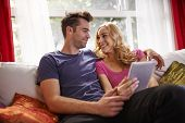 stock photo of futon  - couple using tablet to buy stuff online - JPG