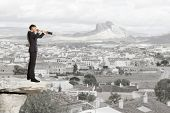 Businessman looks through a telescope. Concept for business