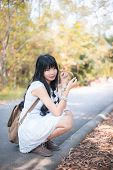 A Cute Asian Thai Girl Is Sitting And Holding A Dry Leaf And Making Eye Contact