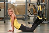Fitness TRX training exercises at gym woman