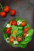 Bowl of fresh colorful salad and tomato cherries on wooden surface