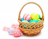 stock photo of gift basket  - Colorful handmade easter eggs in the basket and flowers isolated on a white - JPG