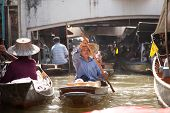 Woman rowing boat in Floating market, Thailand