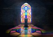 picture of crucifix  - A dim old church interior lit by suns rays penetrating through a colorful stained glass window in the pattern of a crucifix reflecting colours on the floor and a speech pulpit - JPG
