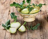 stock photo of kohlrabi  - fresh kohlrabi cabbage and a cut one on a wooden old table - JPG