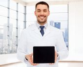 medicine, advertisement and people concept - smiling male doctor showing tablet pc computer blank screen over white room background