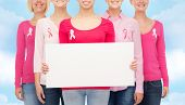 healthcare, people and medicine concept - close up of smiling women in shirts with pink breast cancer awareness ribbons and blank white board over blue sky background