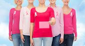 healthcare, people and medicine concept - close up of smiling women in shirts with pink breast cancer awareness ribbons and blank paper card over blue sky background