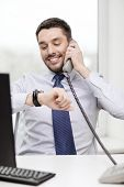 business, office and technology concept - smiling businessman making call and looking at wristwatch at office