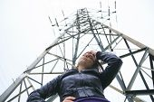 A woman at the bottom of a electricity pylon