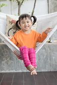 Portrait Of Children Toothy Smiling And Relaxing In Clothes Cradle At Home Living Terrace