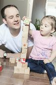 Relaxed father and daughter playing with building blocks on wood