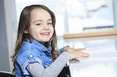 Cute little girl with book at home and smiling