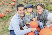 A Family on a field with pumpkins background