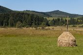 pic of haystack  - Haystack is seen on grass with Carpathian mountains on the background on the summer day - JPG