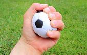 foto of stress-ball  - Hand of man squeezing a small black and white stress ball on green grass background - JPG