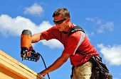 foto of top-gun  - Building contractor worker with a air nail gun nailer working on the corner of the top plate of the first floor walls on a new home construciton project