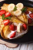 stock photo of crepes  - Delicious crepes with strawberries bananas and cream close - JPG