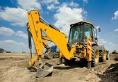 stock photo of excavator  - Wide angle view of excavator standing on ground with blue sky and white clouds in background - JPG