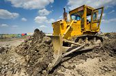 stock photo of earth-mover  - Wide angle view of bulldozer moving earth with blue sky and white clouds in background - JPG