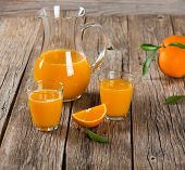 stock photo of pitcher  - Glassfuls and pitcher of orange juice on a old wooden table - JPG