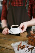 stock photo of cinnamon sticks  - Barista holding cup of black coffee over table with wooden coffee grinder - JPG