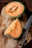 stock photo of cantaloupe  - Cantaloupe ripe melon on wooden surface olive cutting board - JPG