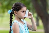 stock photo of inhalant  - Little girl using his inhaler on a sunny day - JPG