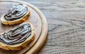 stock photo of baguette  - Slices Of Baguette With Chocolate Cream On The Wooden Board - JPG