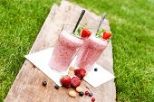 image of oblique  - 2 glasses with a berry milkshake and decoration on an old wooden board lying on grass landscape oblique - JPG