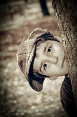 stock photo of newsboy  - Young boy with newsboy cap sneaking behind a tree and playing detective - JPG