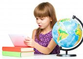 pic of geography  - Surprised young girl is using tablet while studying geography - JPG