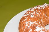 image of icing  - A slice of freshly baked ring cake with icing sugar on green blurred background  - JPG