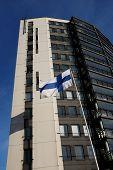 pic of flutter  - fluttering national flag of Finland beside modern building vertical - JPG