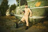 pic of helicopters  - Young serious pilot posing near the helicopter - JPG