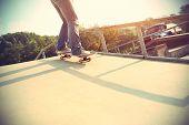 pic of skateboard  - skateboarder riding on skateboard at skatepark ramp - JPG