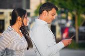 stock photo of adultery  - Closeup portrait woman watching man over shoulder happily texting someone else isolated outdoors background - JPG