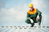 foto of millwright  - worker builder with hand drill at metal profile roof installation - JPG